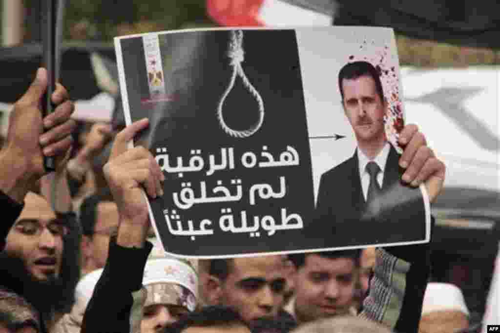 """People hold up a poster showing Syrian President Bashar al-Assad during a protest in front of the Syrian embassy in Cairo, Egypt, Friday, Feb. 17, 2012. The poster reads: """" That's why this neck was created long"""". (AP Photo/Amr Nabil)"""