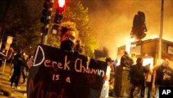 Muandamanaji abeba bango huku majengo yakiteketea Minneapolis