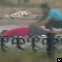 A protester crouches near the body of a man lying on the ground in Hama in this still image taken from video posted on a social media website on August 4, 2011 (Reuters cannot independently verify the content of the video)