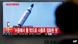 Putnik na železničkoj stasnici u Seulu posmatra izveštaj na televiziji o balističkoj probi Severne Koreje