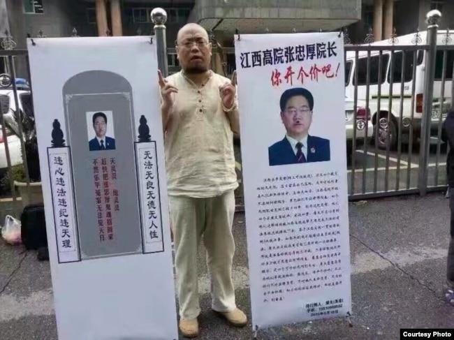吴淦在江西高院前摆易拉宝。(照片来源:现场活动人士)