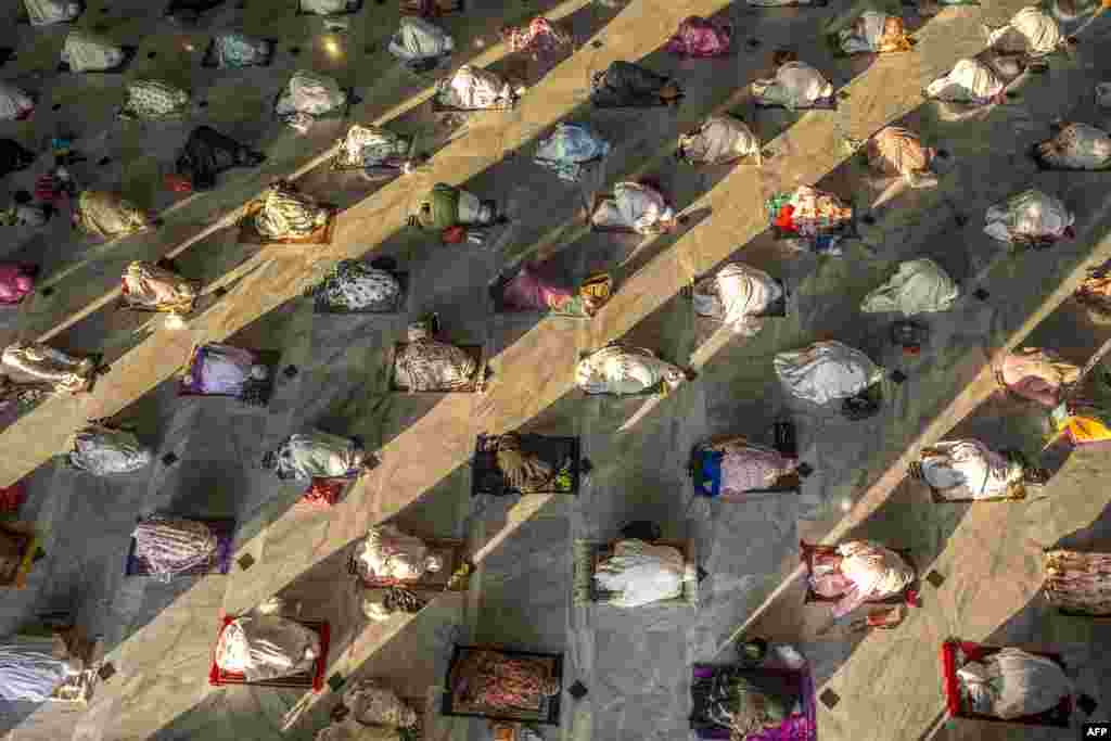 Muslims attend Eid al-Adha prayers with social distancing as a preventive measure against the COVID-19 coronavirus at a mosque in Surabaya in East Java, Indonesia.