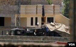 Kendaraan-kendaraan pasukan keamanan diparkir di dalam kompleks tempat tinggal bin Laden, Senin (2/5).