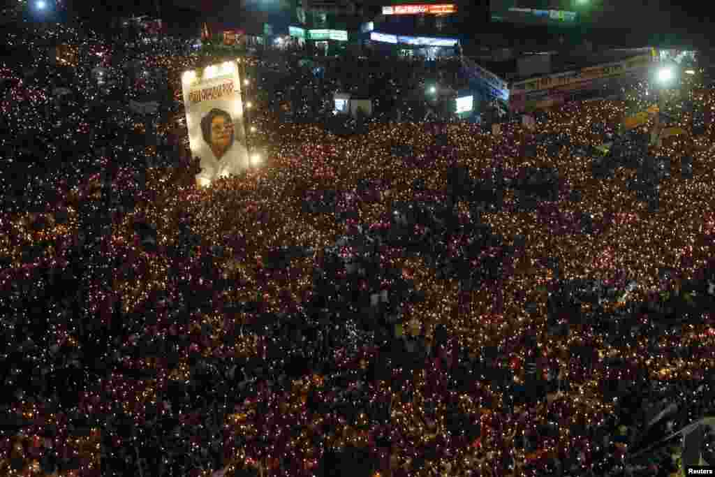 People attend a mass candlelight vigil around a portrait of Jahanara Imam, the late political activist pioneer widely known for bringing the accused of committing war crimes in the Bangladesh Liberation War to trial, at Shahbagh intersection in Dhaka, Bangladesh.