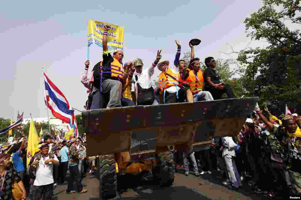 Anti-government protesters celebrate on a front loader used to knock down a concrete barricade outside the Government House in Bangkok Dec. 9, 2013.