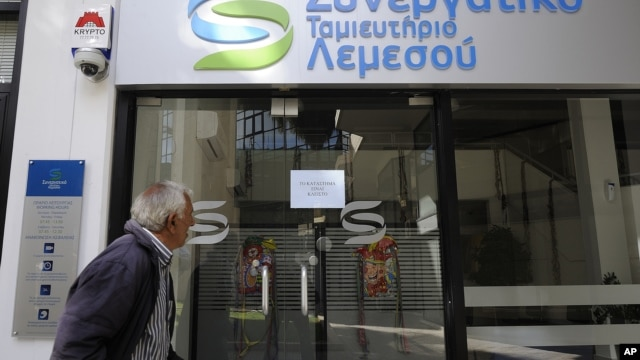 An elderly man holds his bank passbook as he looks through the windows of a closed cooperative bank shop in Limassol, Cyprus,  Mar. 16, 2013.