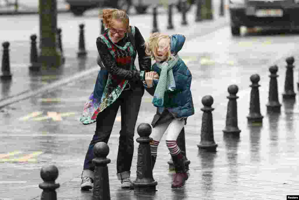 A woman and her daughter struggle against strong winds and rain in central Brussels, Belgium. According to local media, the winds could reach speeds of over 100 km per hour (62 miles per hour).