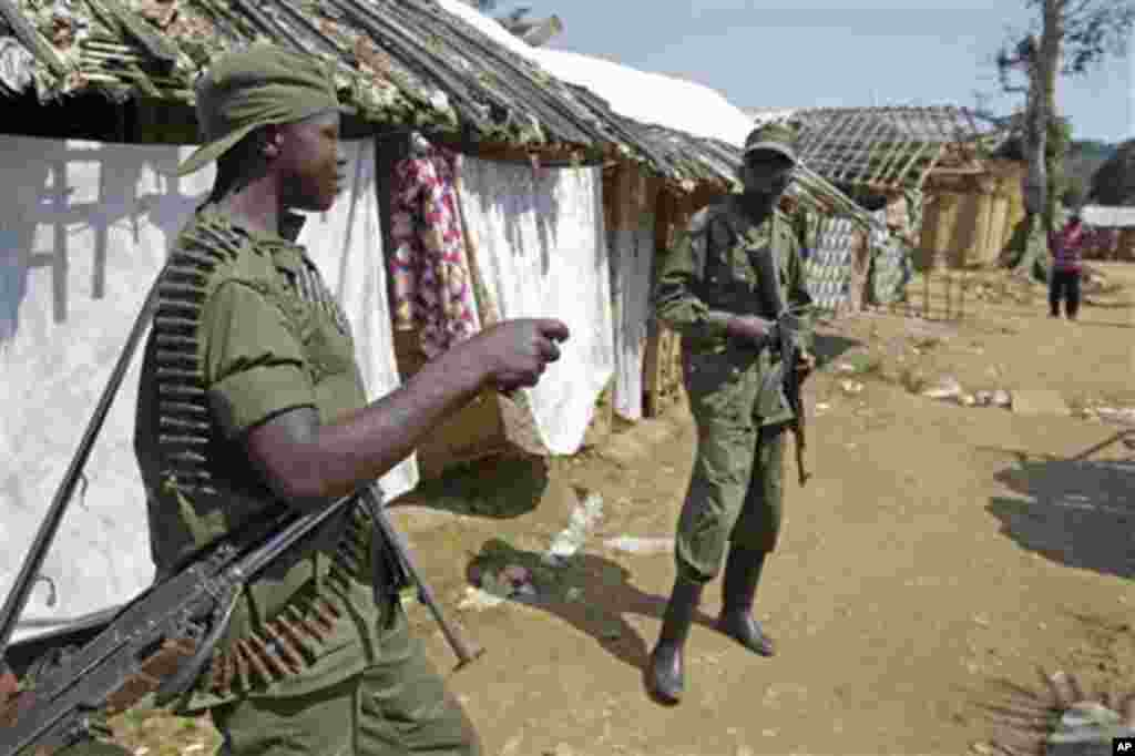 Congo troops provide security for villagers on the outskirts of Walikale, Congo, Friday, Sept. 17, 2010, where violence in this corner of Congo is reported to be spiraling out of control. Some hundreds of victims of a mass gang-rape has drawn internationa