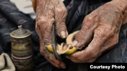 FILE - A 90-year-old Thai woman uses a pair of traditional metal cutters to slice open an areca nut that she will then chew mixed with betel leaf and lime paste to form a mild stimulant. (Photo taken by Matthew Richards/Thailand/VOA reader)