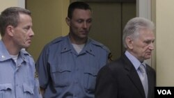 Flanked by UN security guards, Momcilo Perisic, the former chief of staff of the Yugoslav army, right, enters the court room of the Yugoslav War Crimes Tribunal in The Hague, to hear the verdict of the court, September 6, 2011.