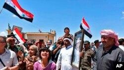 지난 15일 반군이 떠난 시리아 홈스에서 주민들이 국기를 들고 시리아 정부군의 귀환을 환영하고 있다.
