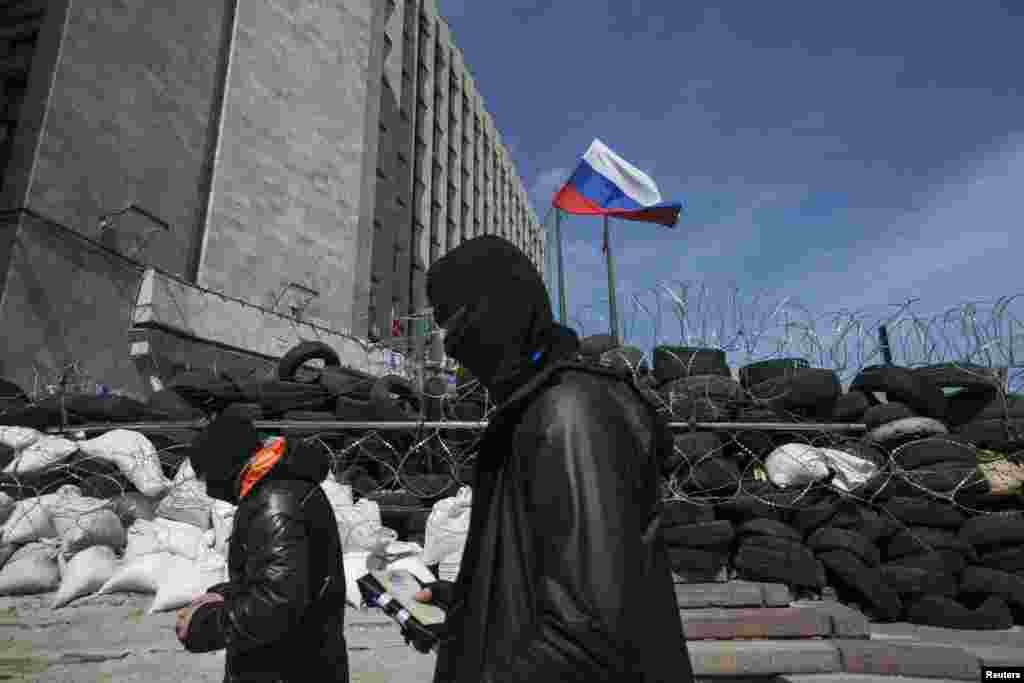 An agreement reached last week to avert wider conflict in Ukraine was faltering as the new week began, with pro-Moscow separatist gunmen showing no sign of surrendering government buildings they had seized. Here masked pro-Russian men walk past a barricade outside a regional government building in Donetsk, Ukraine, April 21, 2014.