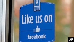 "FILE - A sign with Facebook's ""Like"" logo is posted at Facebook headquarters in Menlo Park, California."