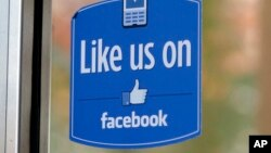 "FILE - a sign with Facebook's ""Like"" logo is posted at Facebook headquarters near the office for the company's User Operations Safety Team in Menlo Park, Calif."