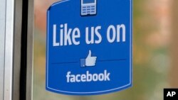 "FILE - A sign with Facebook's ""Like"" logo is posted at Facebook headquarters in Menlo Park, California, Dec. 13, 2011."