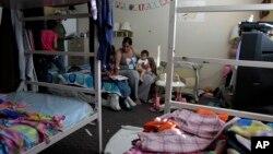 """Antoine Reyes (dua dari kiri) dan istrinya Susan (tengah) membantu anak-anaknya mengerjakan PR di tempat penampungan """"Union Rescue Mission"""" di Los Angeles (Foto: dok). Hasil sensus menunjukkan dari enam orang Amerika hidup pada atau dibawah garis kemiskinan tahun lalu."""