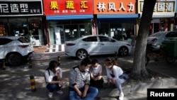 2020年5月13日,北京一个招聘服务中心外几名失业年轻人正在用手机寻找招聘信息。