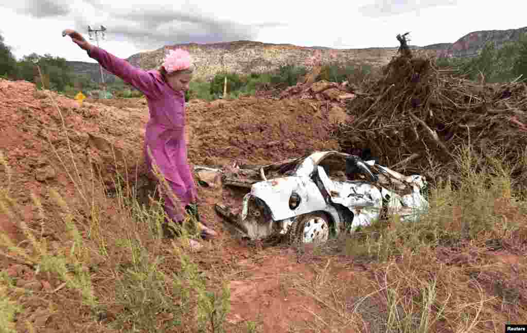 "A girl jumps off a mound of dirt that was piled up with one of the vehicles found after a flash flood, in Hildale, Utah, Sept. 15, 2015. Flash floods killed nine people near Utah's border with Arizona when a ""large wall of water"" triggered by heavy rain pounding nearby canyons swept them away in their cars, officials said."