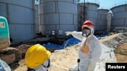 Japan's Economy, Trade and Industry Minister Toshimitsu Motegi (R), wearing a protective suit and a mask, inspects contaminated water tanks at the tsunami-crippled Fukushima Daiichi nuclear power plant in Fukushima prefecture August 26, 2013, in this phot