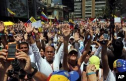 Demonstrators raise their arms in unison during a demonstration honoring the victims who died in last month's anti-government protests, in Caracas, Venezuela, March 4, 2014.