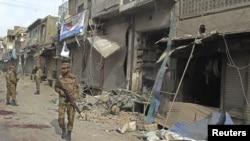 Petugas keamanan memeriksa sekitar lokasi kejadian ledakan bom di depan sebuah toko di dekat prosesi Syiah di Dera Ismail Khan, barat laut Pakistan (25/11). Ledakan ini menewaskan 5 orang dan melukai 70 orang lainnya.