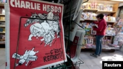 "FILE - The front page of satirical French weekly Charlie Hebdo entitled ""C'est Reparti"" (""Here we go again""), is displayed at a kiosk in Nice, France."