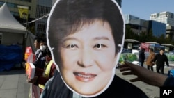 A South Korean protester wears a mask of South Korean President Park Geun-hye during a rally calling for Park to step down in downtown Seoul, South Korea, Nov. 11, 2016. Tens of thousands of South Koreans are expected to march in Seoul to demand Park's resignation on Saturday over a snowballing influence-peddling scandal involving Park's longtime confidante.