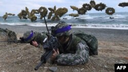 South Korean Marines take position on a beach as amphibious assault vehicles fire smoke shells during a joint landing operation by US and South Korean Marines in the southeastern port of Pohang on April 2, 2017.