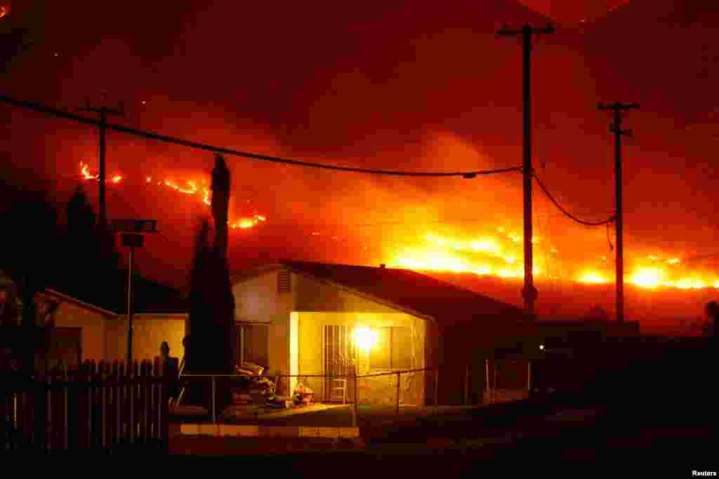The Silver Fire burns near homes in the community of Cabazon in the early morning hours, August 8, 2013. The fire broke out shortly after 2 p.m. near a back-country road about 90 miles (145 km) outside Los Angeles.