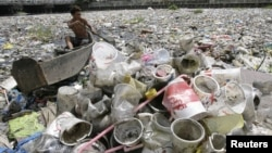A boy collects plastic from a garbage-covered river in Manila March 21, 2010.