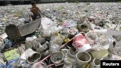 Một bé trai nhặt các đồ nhựa trôi trên con sông phủ đầy rác ở Manila