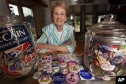 FILE - Judy Galluzzo poses with campaign buttons she's collected over the years, in Salem, N.H.