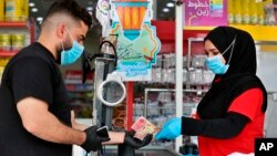 In this Saturday, May, 2, 2020, photo, a man uses banknotes to pay for his purchases at the mall in Basra, Iraq. The coronavirus pandemic has renewed debate about the use of paper money and coins. (AP Photo/Nabil al-Jurani)