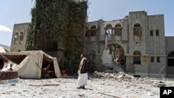 FILE - A man loyal to former Yemeni president Ali Abdullah Saleh stands guard at Saleh's house destroyed by a Saudi-led airstrike in Sanaa, Yemen, Sunday, May 10, 2015.