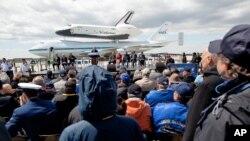 ຍານອະວະກາດໄປກັບ Enterprise ທີ່ຢອງຢູ່ເທິງເຮືອບິນໂບອິ້ງ 747 ຂະໜາດໃຫຍ່ຂອງອົງການ NASA ເດີນທາງໄປເຖິງສະໜາມບິນນາໆຊາດ JFK ທ່າມກາງການໄປຕ້ອນຮັບຂອງຝູງຊົນ (27 ເມສາ 2012)