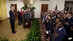 President Barack Obama says the Pledge of Allegiance during a naturalization ceremony for active duty service members in the East Room of the White House in Washington, Wednesday, July 4, 2012. (AP Photo/Evan Vucci)