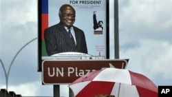 People walk under an election poster of the ruling South West African People's Organization (SWAPO), showing the incumbent President Hifikepunye Pohamba in Katatura, outside Windhoek, 25 Nov 2009