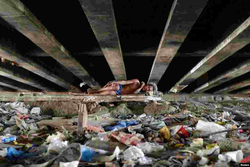 فقر در مانیل، پایتخت فیلیپین. مردی، زیر پل خوابیده است.