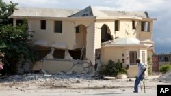FILE - A man walks on crutches past a building destroyed by the earthquake in Leogane, Haiti, Dec. 12, 2010.