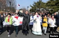 Presiden Korea Selatan Moon Jae-in dan istrinya Kim Jung-Sook melakukan pawai dengan berjalan bersama para peserta dalam upacara peringatan HUT ke-99 Gerakan Kemerdekaan Satu Maret melawan penjajahan Jepang di Seoul, Korea Selatan, 1 Maret 2018.