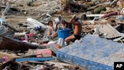 Warga mandi di dekat puing-puing rumah mereka yang hancur karena gempa.