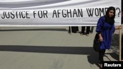 Seorang wanita berunjuk rasa di Kabul (11/7) dengan membawa spanduk yang menyuarakan protes atas eksekusi seorang perempuan oleh anggota Taliban di wilayah Parwan, Afghanistan.
