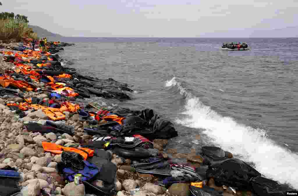 Syrian refugees arrive on a beach covered with life vests and deflated dinghies on the Greek island of Lesbos.
