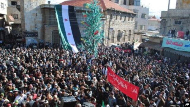 Anti-Syrian regime protesters gather at a square as they hold an Arabic banner, center, reading, 'hey, the miserable, the tyrant, what else,' during a demonstration at the mountain resort town of Zabadani, Syria, near the Lebanese border, January 20, 2012