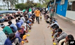 Warga India yang tunawisma dan miskin menerima makanan di penampungan pemerintah di New Delhi, India, Kamis, 26 Maret 2020. (Foto: AP)