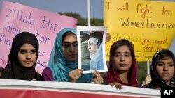 Para perempuan Pakistan membawa poster Malala Yousufzai dalam unjuk rasa mengecam serangan Taliban di Islamabad (13/10).