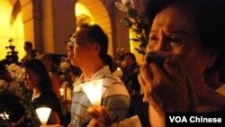 參加者手持蠟燭及鮮花為李旺陽離奇死亡落淚