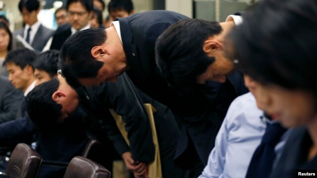 Mizuho Financial Group President Yasuhiro Sato (C) and other company officials bow at a news conference at the Bank of Japan headquarters in Tokyo, Oct. 28, 2013.
