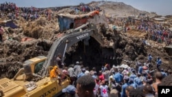 FILE - rescuers work at the scene of a garbage landslide, on the outskirts of the capital Addis Ababa, in Ethiopia.