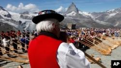 Alphorn blowers in Zermatt play together on the Gornergrat Mountain with the Matterhorn mountain in the background.